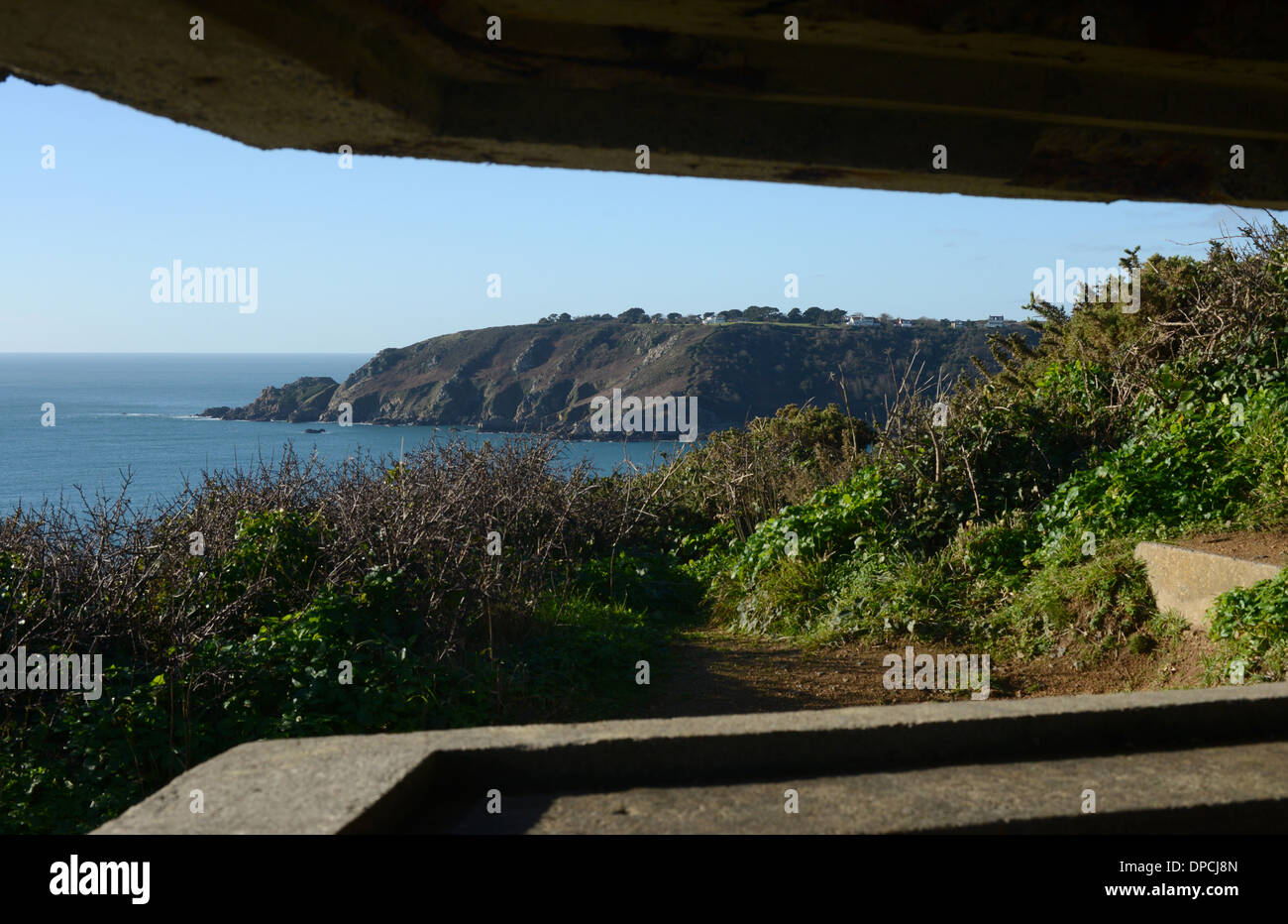 View from inside La Moye Battery, a WW2 gun battery, overlooking Moulin Huet Bay and Saints Bay in Guernsey, Channel Islands. - Stock Image