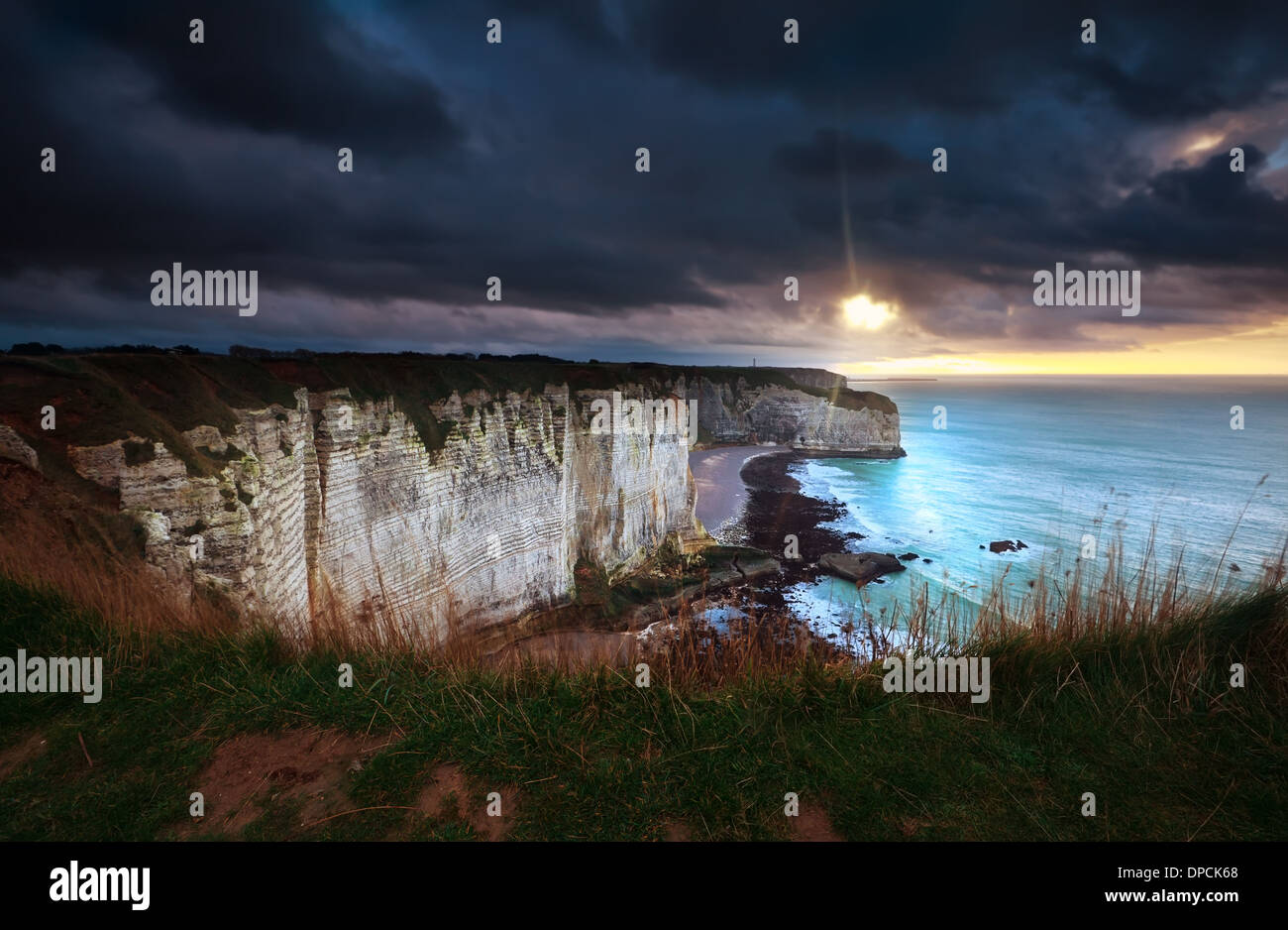 sunshine and storm sky over cliffs in ocean, Etretat, France - Stock Image