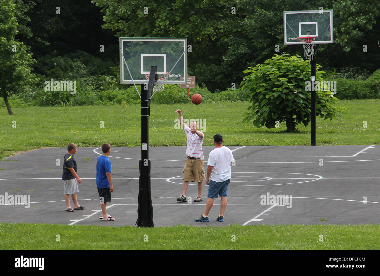 Young men playing basketball in park Indiana - Stock Image