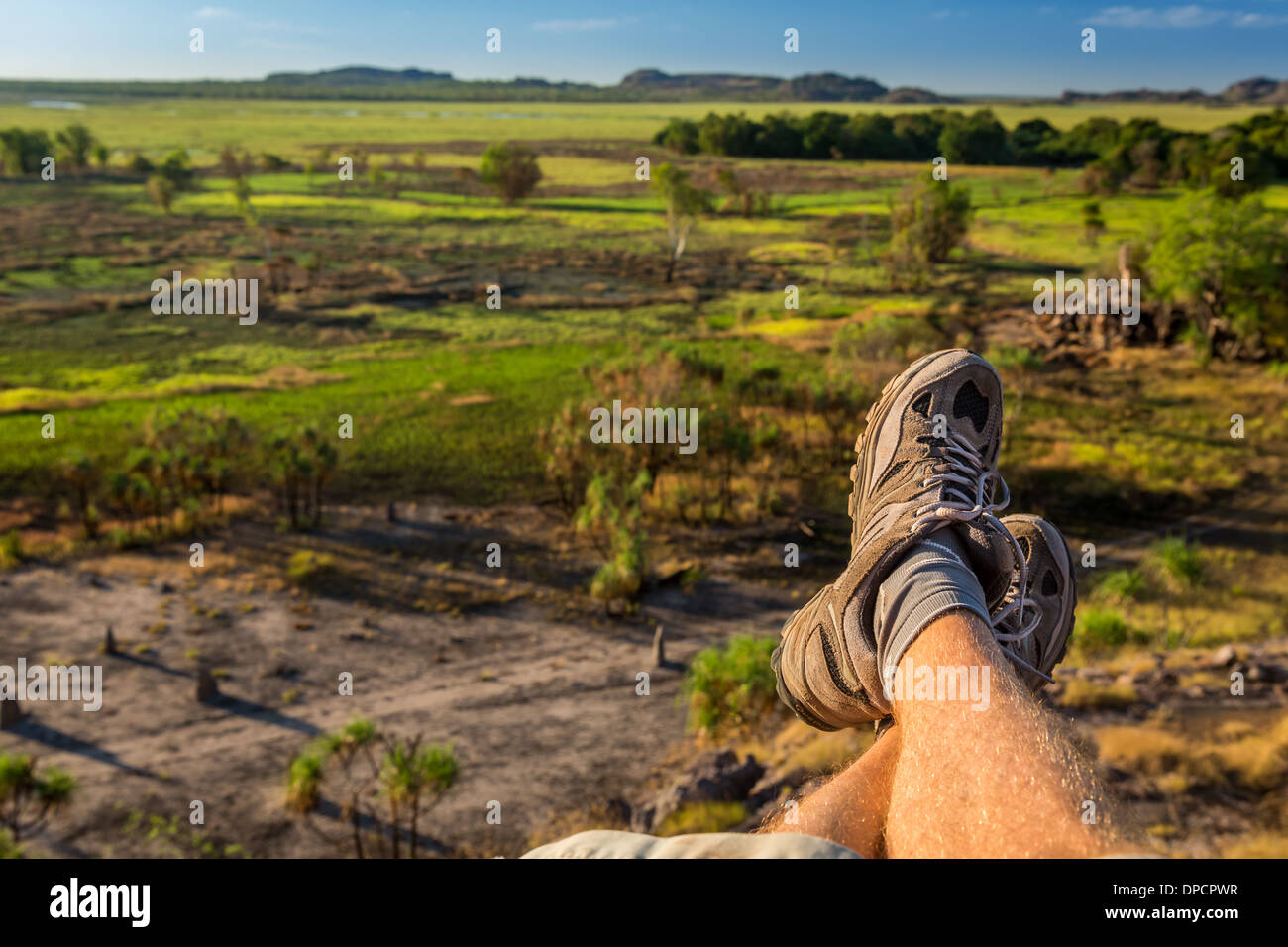 Man's legs with view of Nadab floodplain, Nadab lookout, Ubirr, East Alligator region, Northern Territory, Australia - Stock Image
