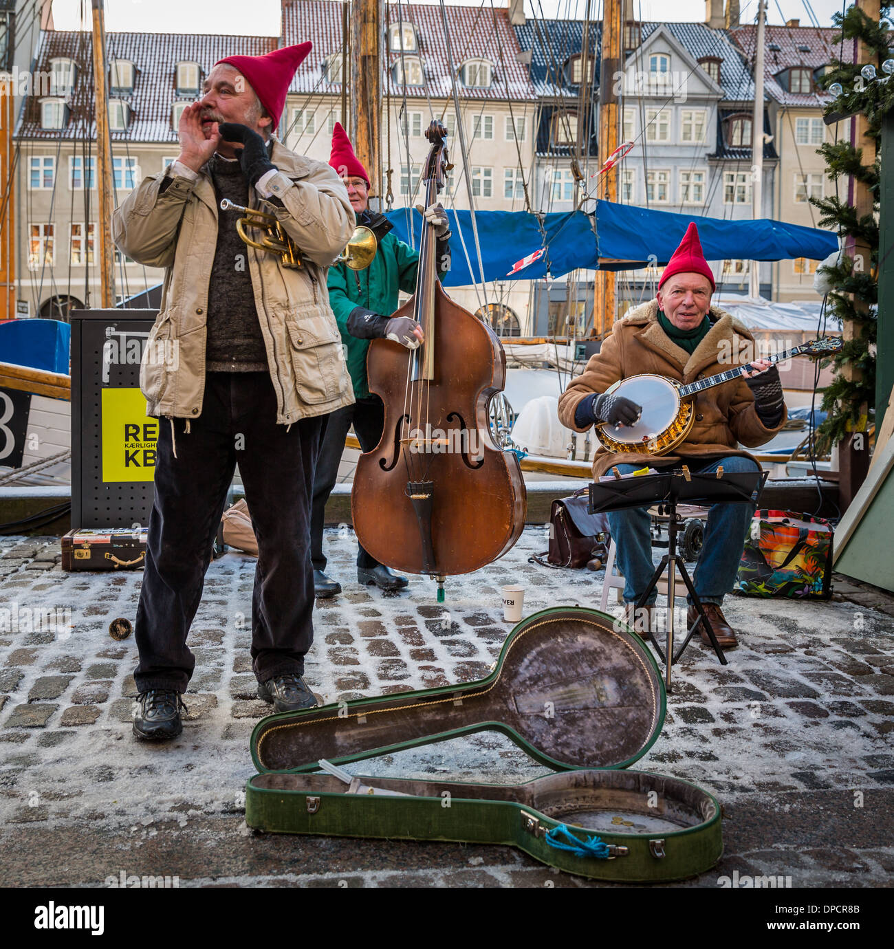 Three street musicians playing Christmas music, Nyhavn, Copenhagen, Denmark - Stock Image