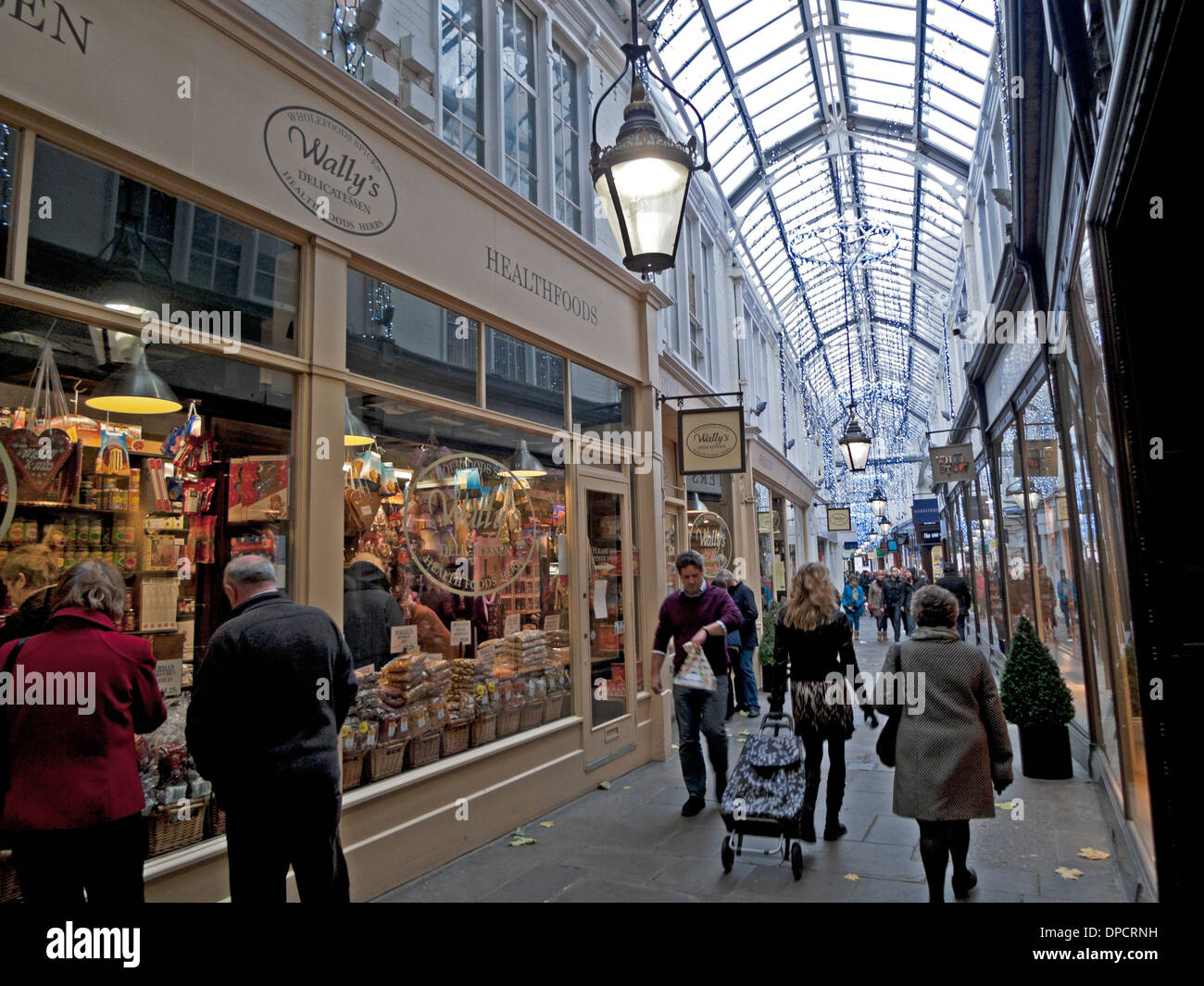 Shoppers walking past Wally's delicatessen in Royal Arcade  at Christmas time in Cardiff City Centre Wales UK KATHY DEWITT - Stock Image