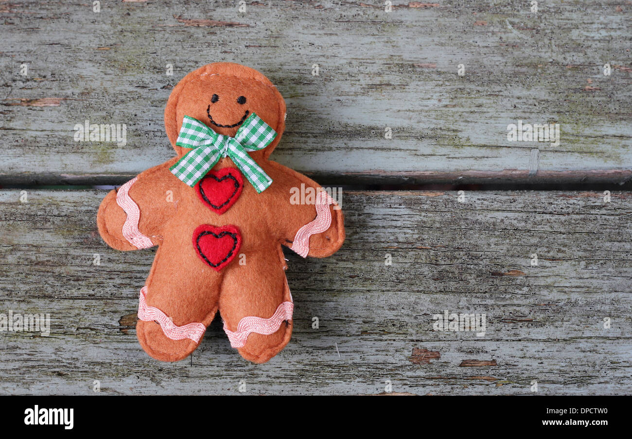 Smiling gingerbread man laying on shabby chic wooden bench - Stock Image