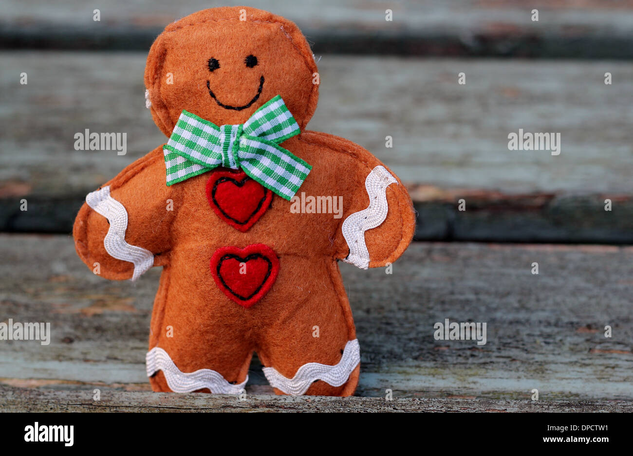 Cute gingerbread man with a smile and red heart buttons stood on shabby chic bench - Stock Image