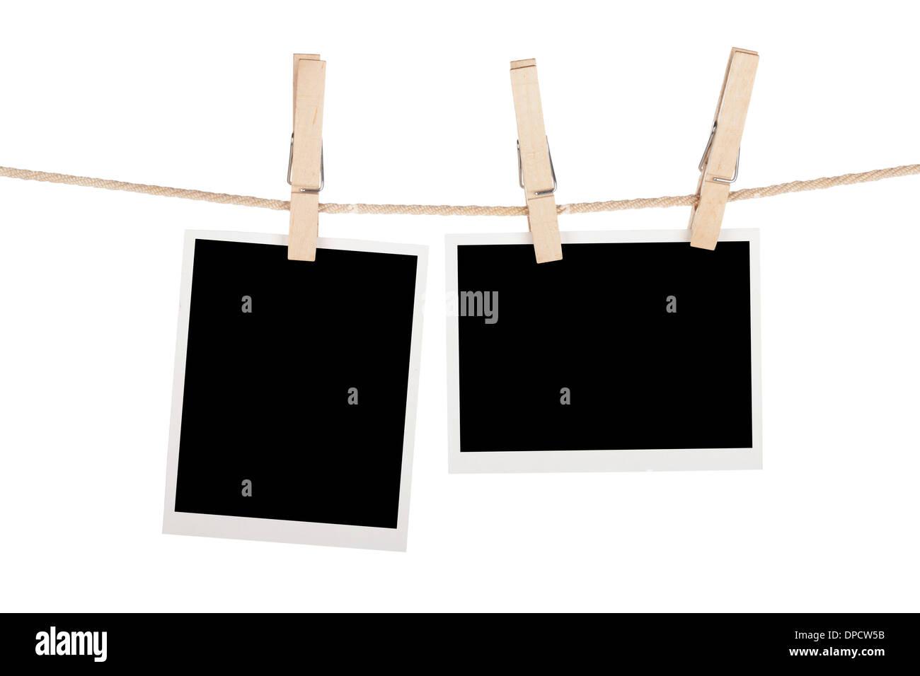 Blank photos hanging on clothesline. Isolated on white background - Stock Image