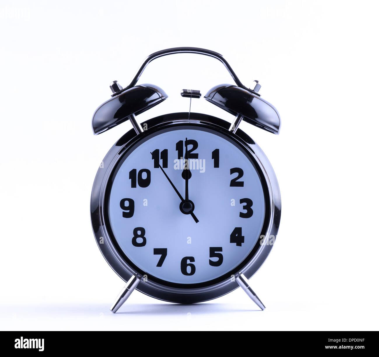Alram clock on white background with twelve o'clock - Stock Image