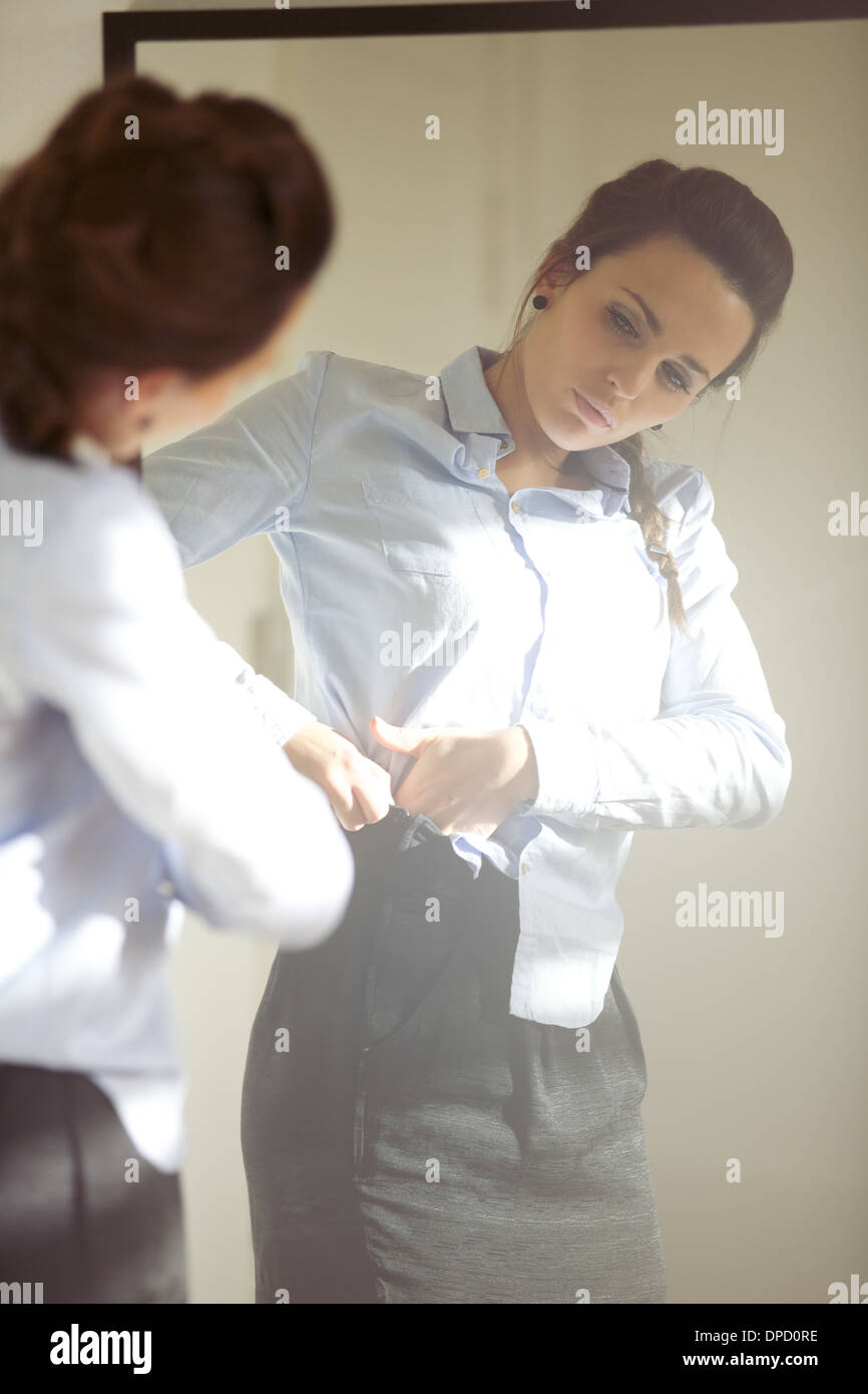 Beautiful young businesswoman wearing business attire in front of mirror. Young caucasian female model getting dressed - Stock Image