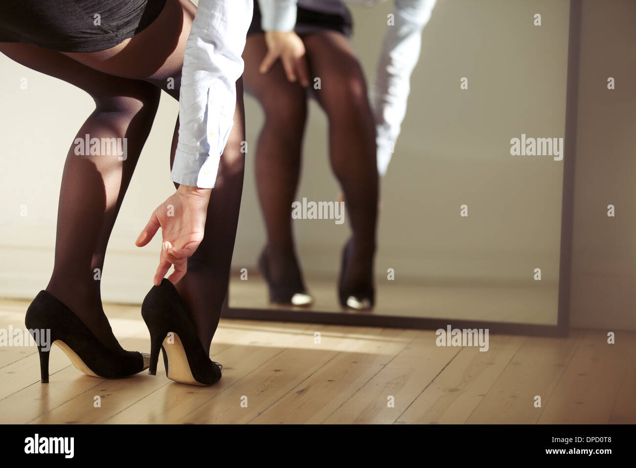 Closeup of female legs wearing high heels shoes. Woman adjusting high heels in front of mirror. - Stock Image