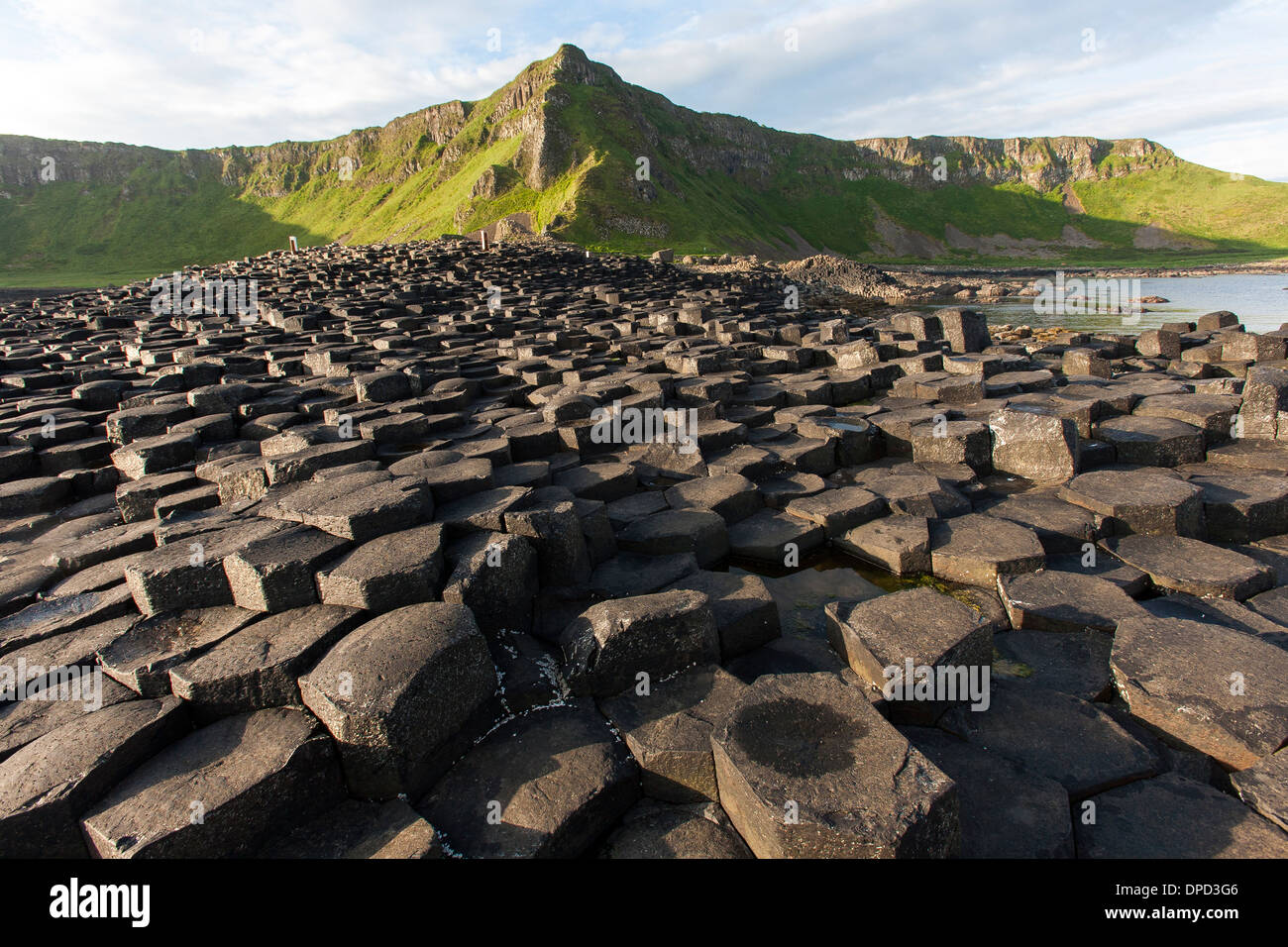 A wide view of the basalt columns that make up the world famous Giants Causeway in County Antrim and close by coastline. - Stock Image