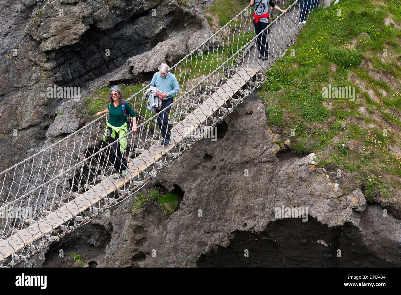 A couple walks carefully halfway across the Carrick-a-Rede rope bridge on the Antrim coast of Northern Ireland. - Stock Image