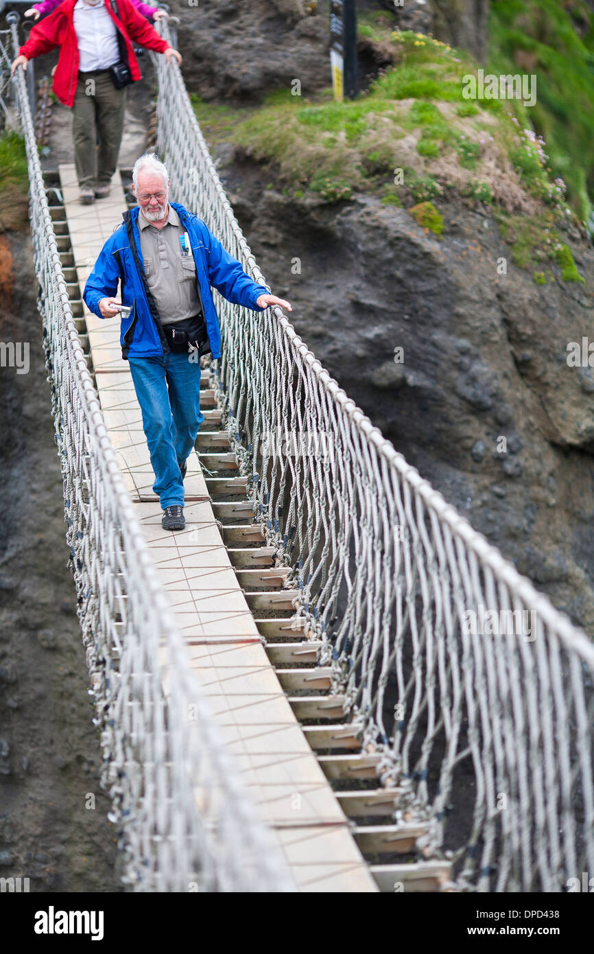 A man walks carefully halfway across the Carrick-a-Rede rope bridge on the Antrim coast of Northern Ireland. - Stock Image