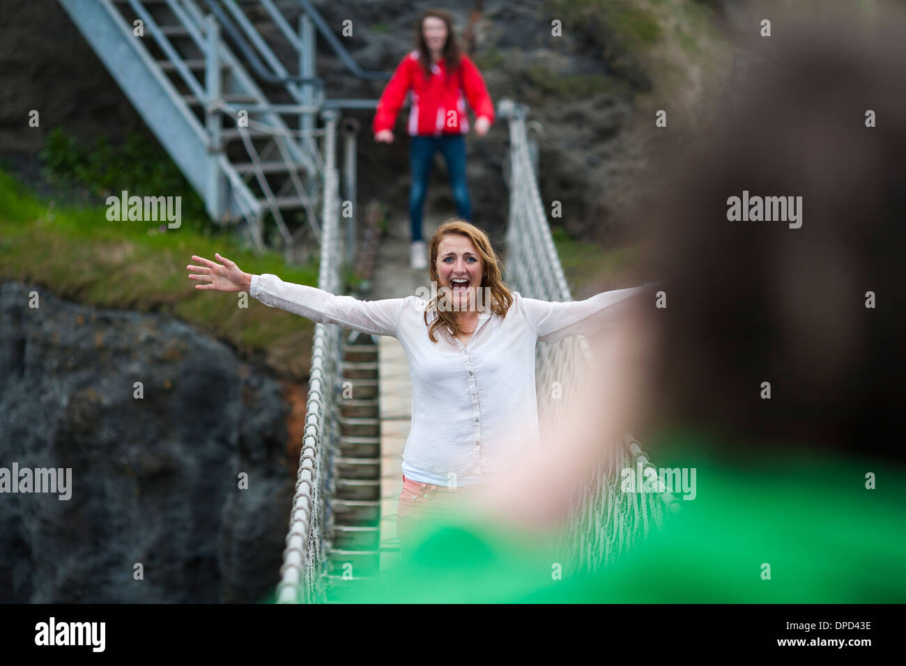 A happy and smiling visitor poses half way across the Carrick-a-Rede rope bridge on the Antrim coast of Northern Ireland. - Stock Image