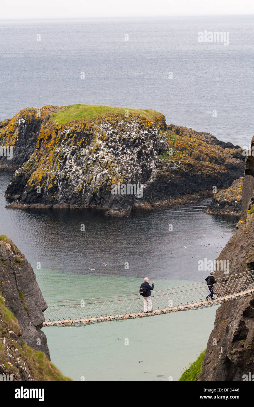Looking down from above the Carrick-a-Rede rope bridge on the Antrim coast of Northern Ireland as a visitor walks across. - Stock Image