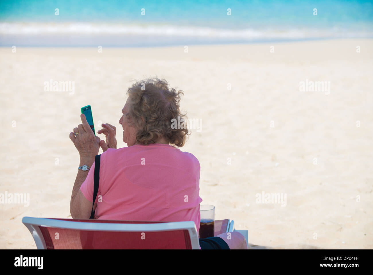 An elderly Caucasian woman sits in a beach chair on Sandcastle Beach, facing the Caribbean sea and plays with her smart phone. - Stock Image