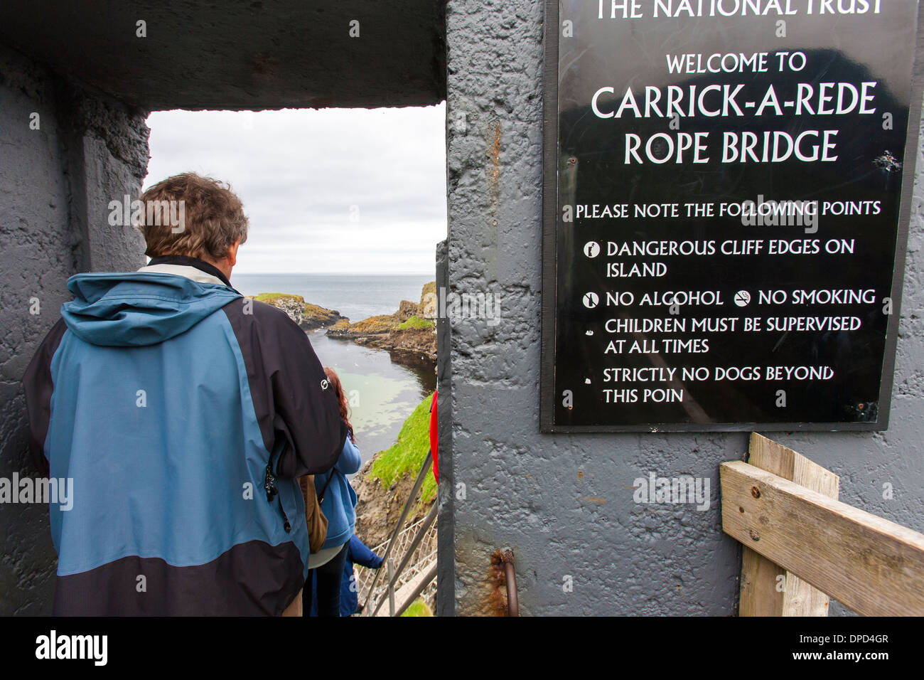A male visitor walks into doorway entrance of the Carrick-a-Rede rope bridge on the Antrim coast of Northern Ireland. - Stock Image