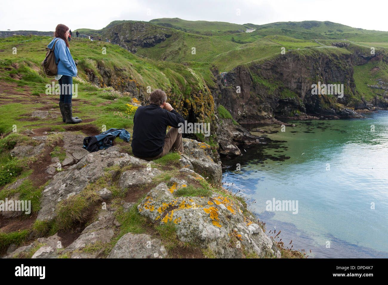 A girl looks at the view along the Antrim coast seen from Carrickarede Island a National Trust property in Northern Ireland. - Stock Image