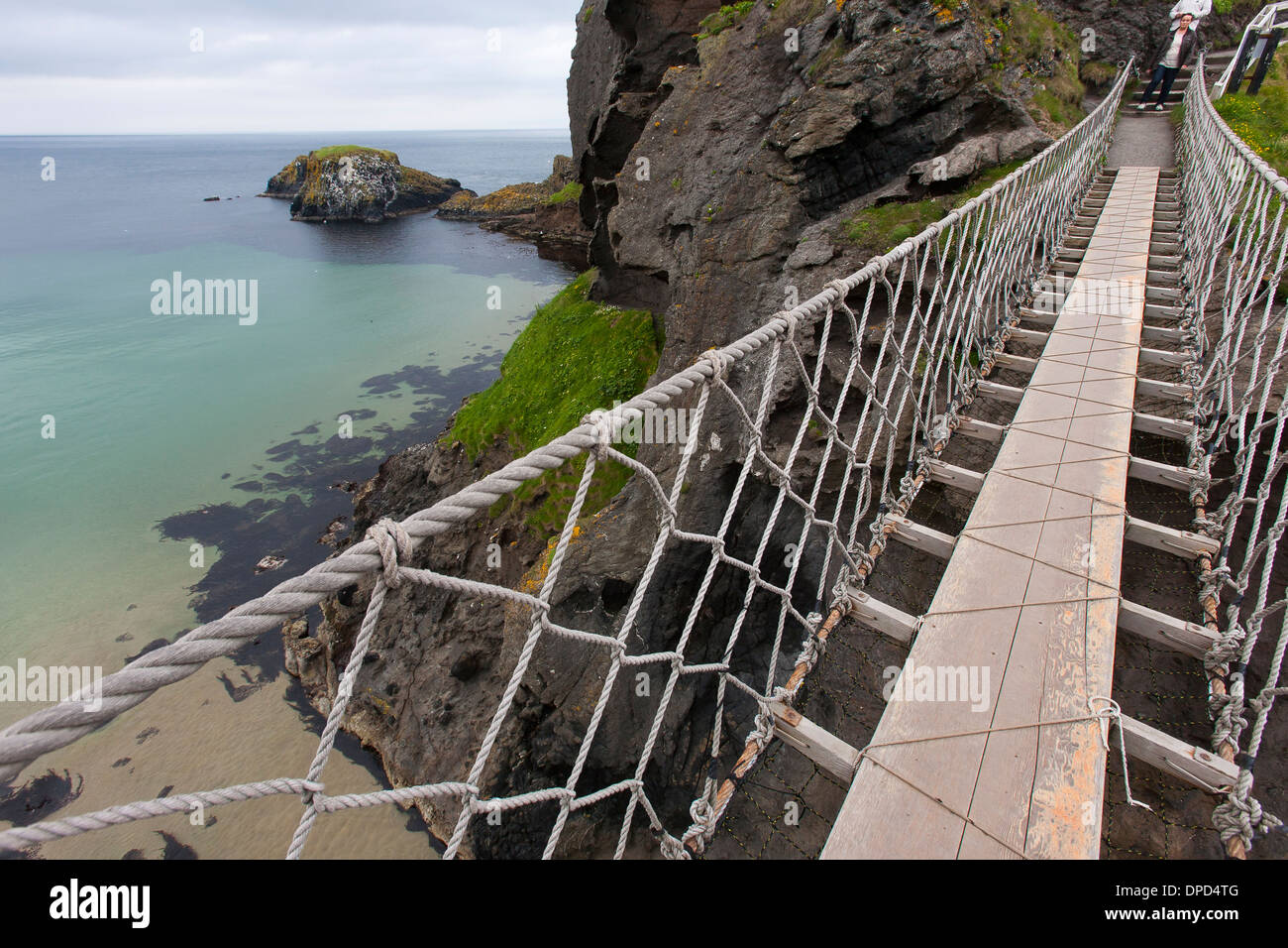 Half way across the Carrick-a-Rede rope bridge on the Antrim coast of Northern Ireland. The bridge connects carrickarede Island - Stock Image