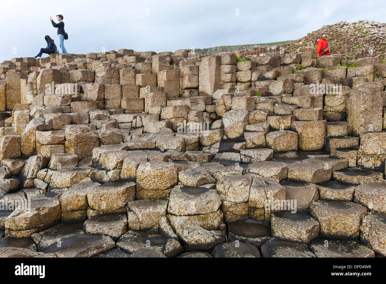 Visitors clamber and climb over the basalt columns that make up the world famous Giants Causeway in County Antrim. - Stock Image