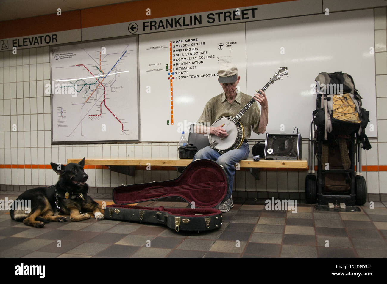 A street performer plays the banjo on the subway accompanied by his dog - Stock Image