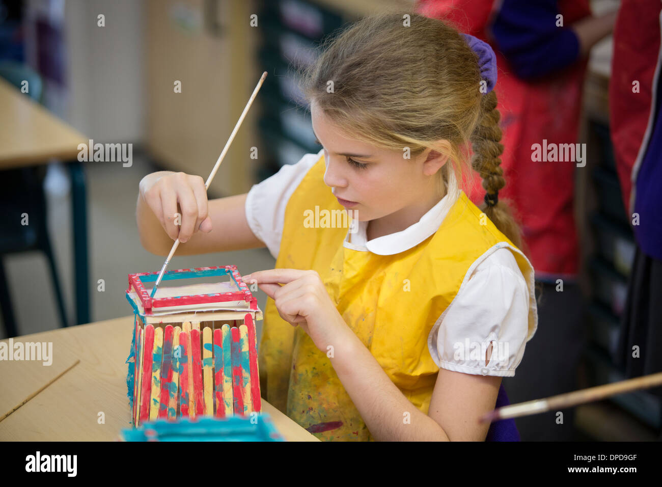 A girl in primary school in the UK making a model of a beach hut in an arts lesson. - Stock Image
