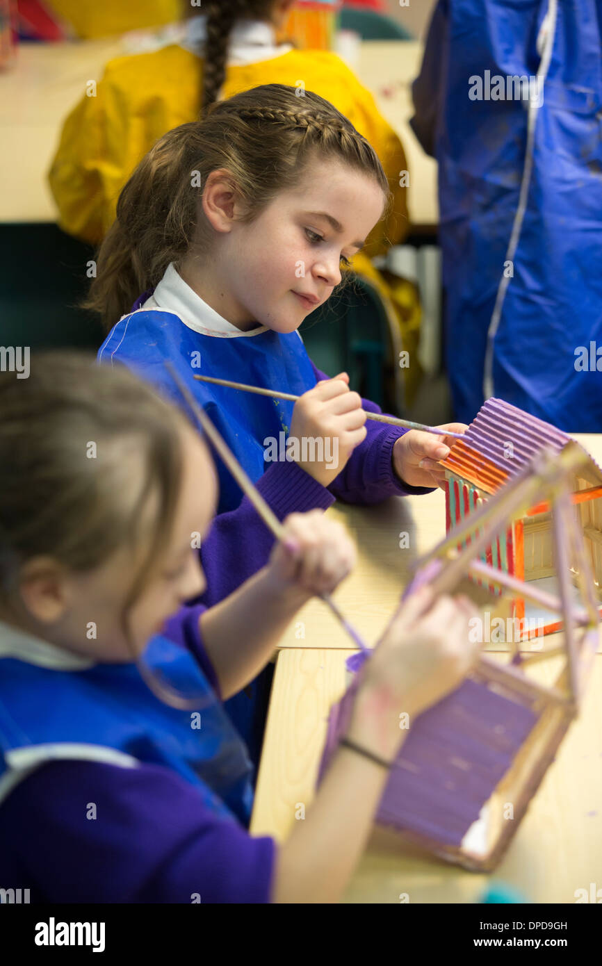 Primary school children in the UK making models of beach huts in an arts lesson. - Stock Image