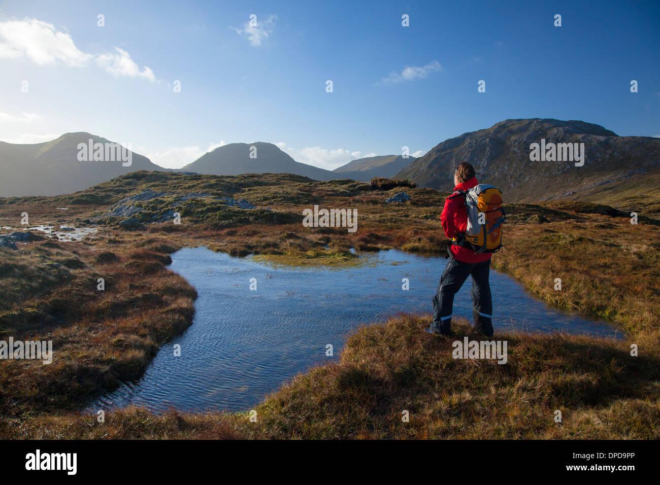 Walker beside a bog pool on a ridge high in the Twelve Bens, Connemara, County Galway, Ireland. - Stock Image