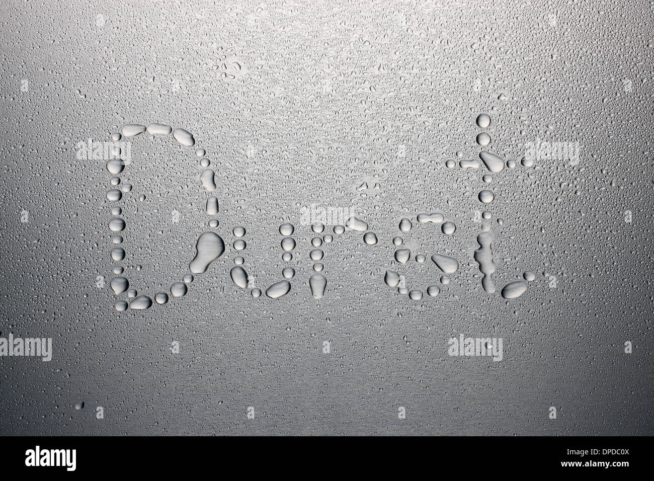 Water drops on metal sheet, forming word thirst - Stock Image