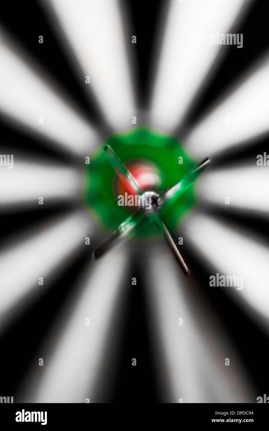A dart in the bull's eye of a dart board - Stock Image