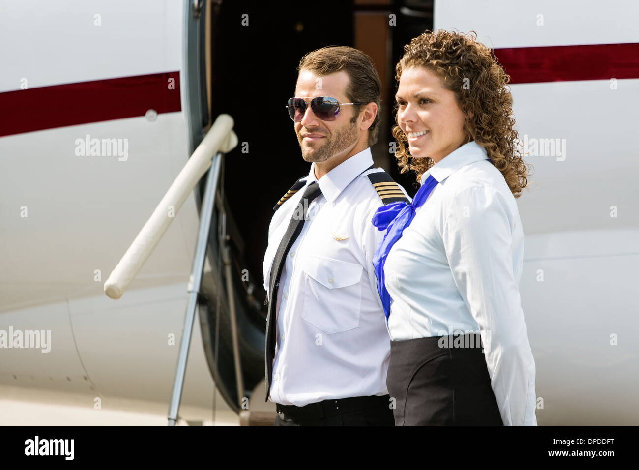 Airhostess And Pilot Looking Away Against Private Jet - Stock Image