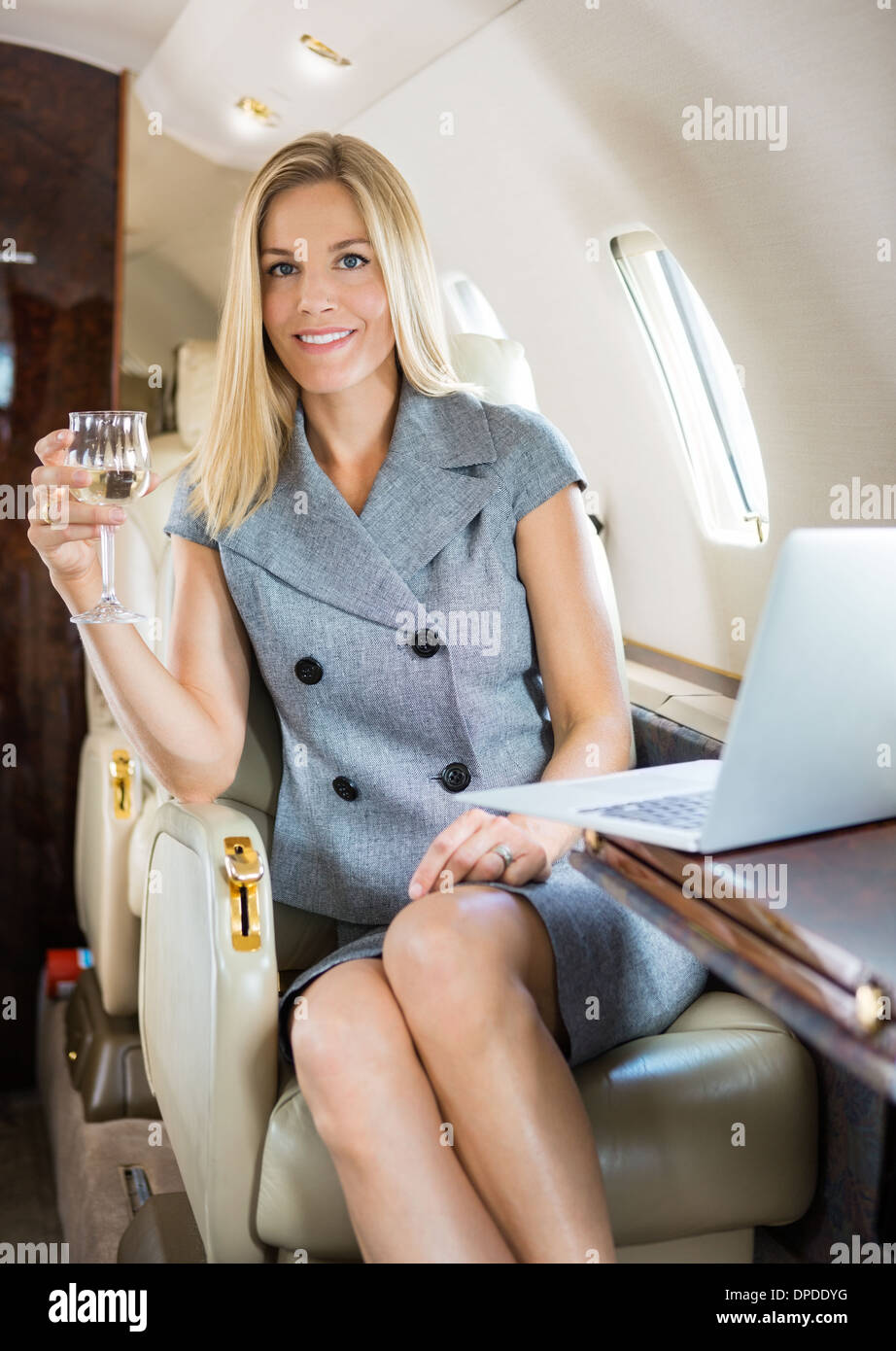 Businesswoman Holding Wineglass In Private Jet - Stock Image
