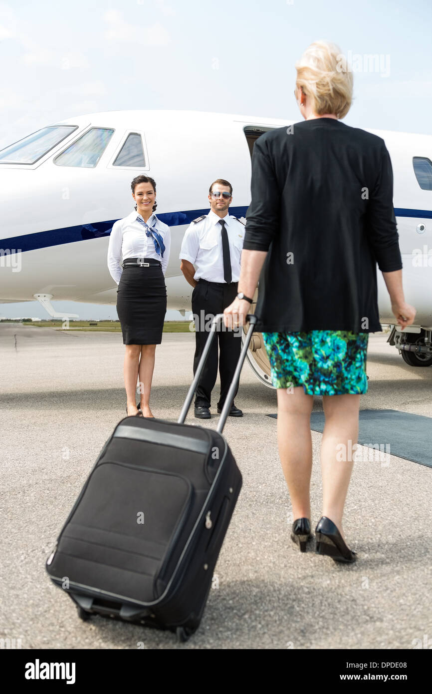 Businesswoman With Luggage Walking Towards Private Plane - Stock Image