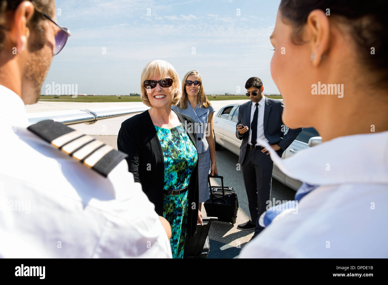 Business Colleagues Greeting Airhostess And Pilot At Terminal - Stock Image