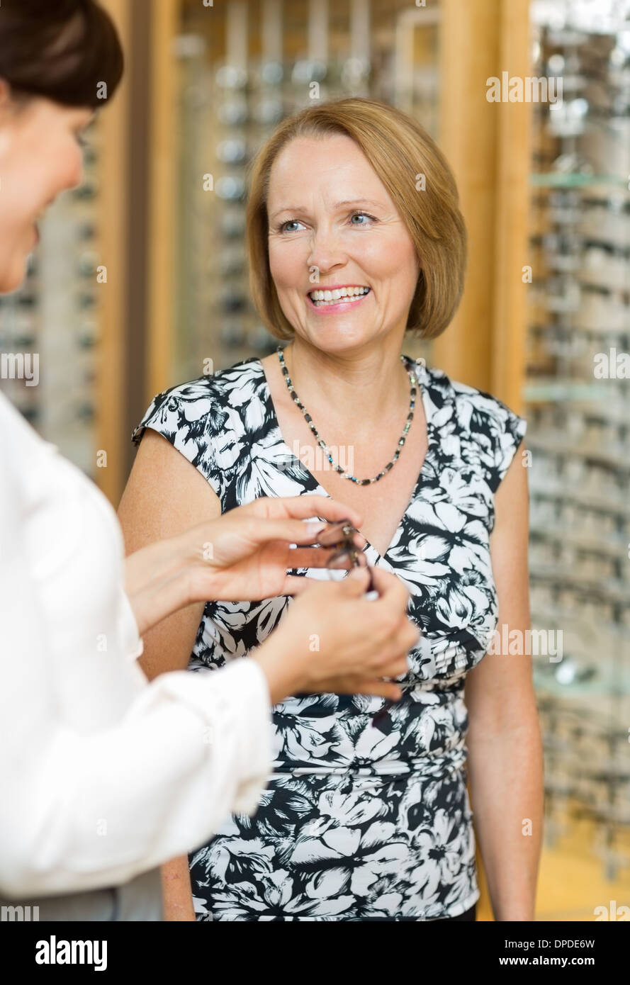 Salesgirl Assisting Senior Customer In Selecting Glasses - Stock Image