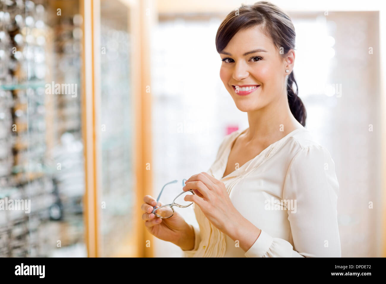 Woman Buying Glasses In Optician Store - Stock Image