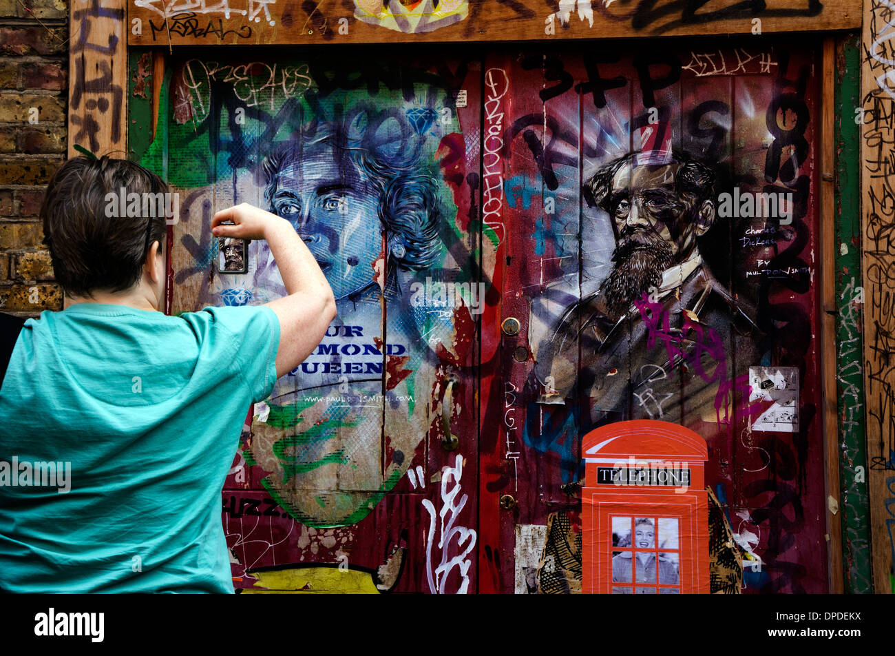 Woman in blue top photographing graffiti with a mobile phone in the Brick Lane area, East London E1 UK Stock Photo