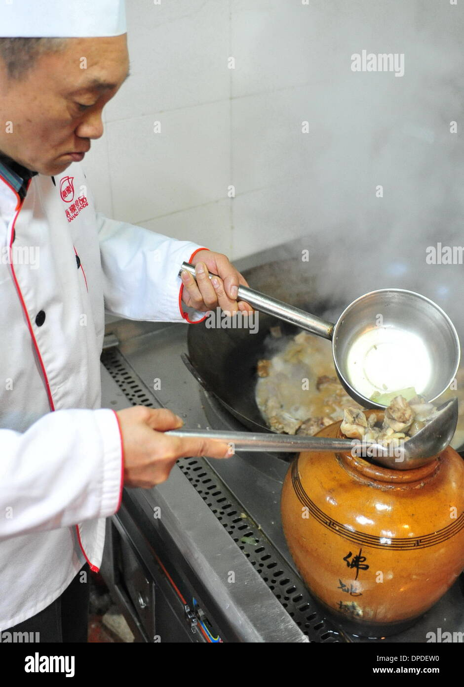 (140113) -- FUZHOU, Jan. 13, 2014 (Xinhua) -- National-top chef Qiang Zhentao puts the ingredient of a dish named Buddha Jumps Over the Wall into a pot, in Fuzhou, capital of southeast China's Fujian Province, Jan. 12, 2014. Buddha Jumps Over the Wall, or Fo Tiao Qiang in Chinese, is a kind of soup or stew which has enjoyed a over 100-year-long worldwide reputation since it was invented in the late Qing Dynasty (1644-1911) by Zheng Chunfa, a chief chef at a local restaurant. The dish's name is referred to an allusion to its ability to entice the vegetarian monks to partake in the meat-based di - Stock Image