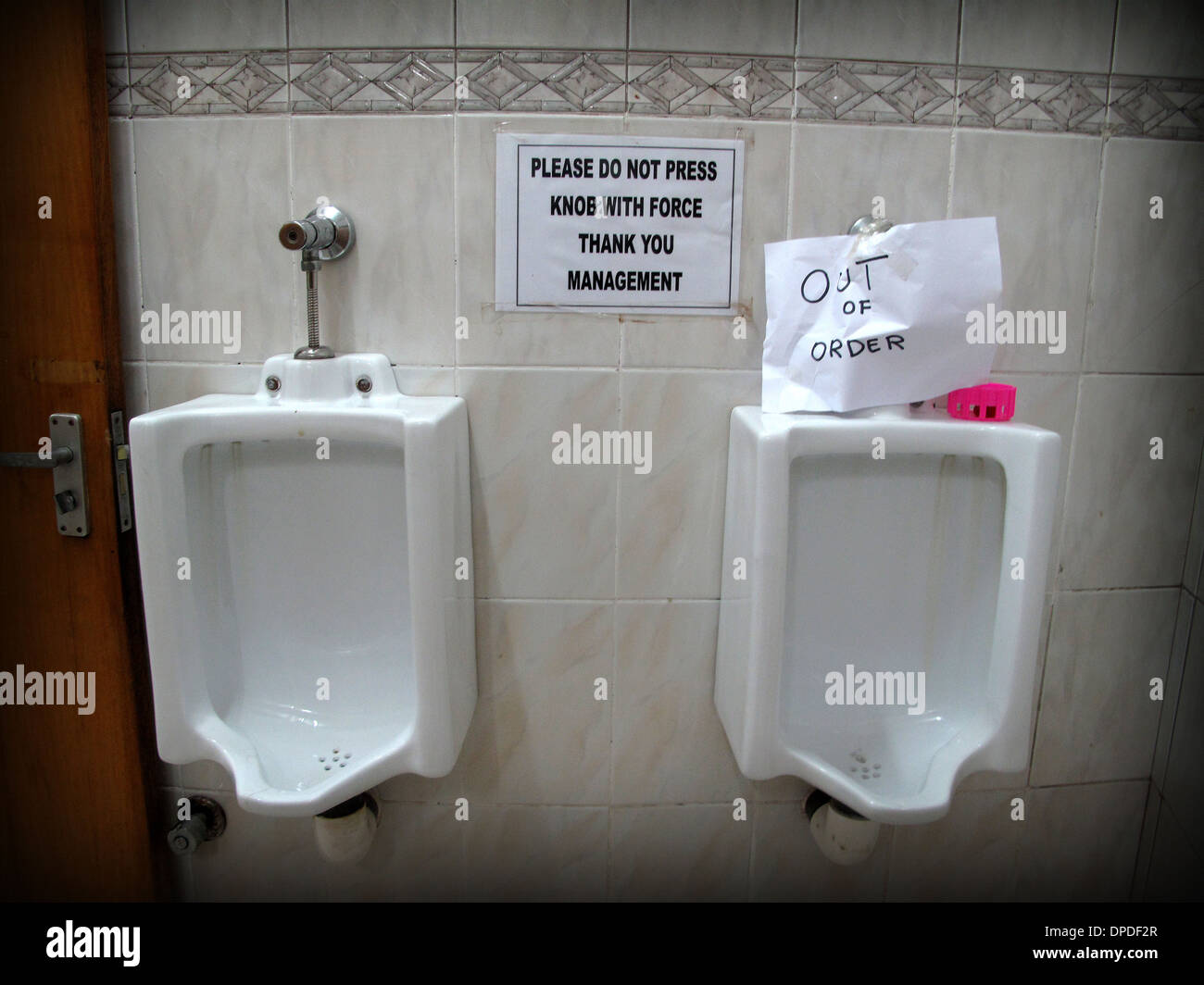 Public urinal in Accra, Ghana with humorous sign - Stock Image
