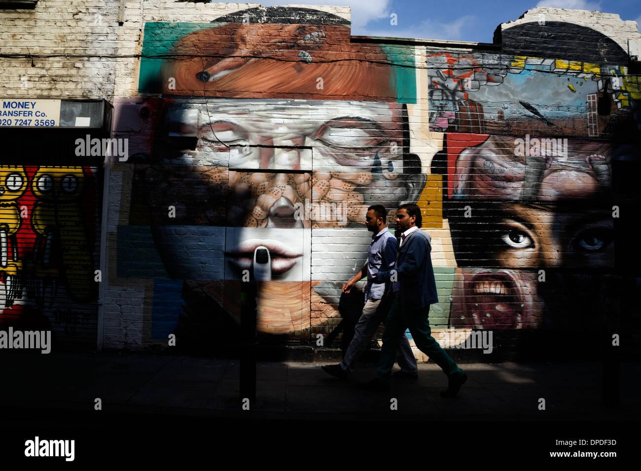 Two young Asian men walking past urban spray can graffiti street art Brick Lane area, East London E1 UK Stock Photo