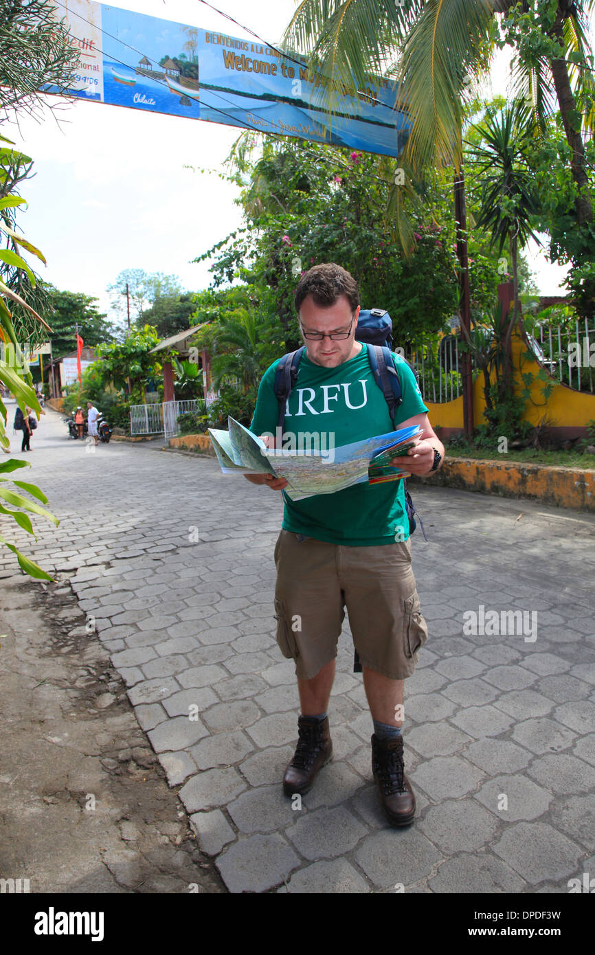 Male backpacker reading a map, Central America. - Stock Image