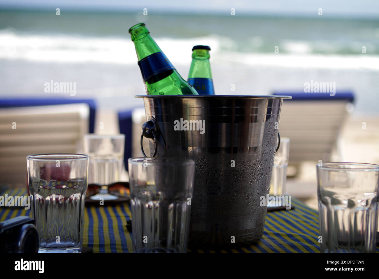 Two bottles in an ice-cooler on a table by the beach - Stock Image
