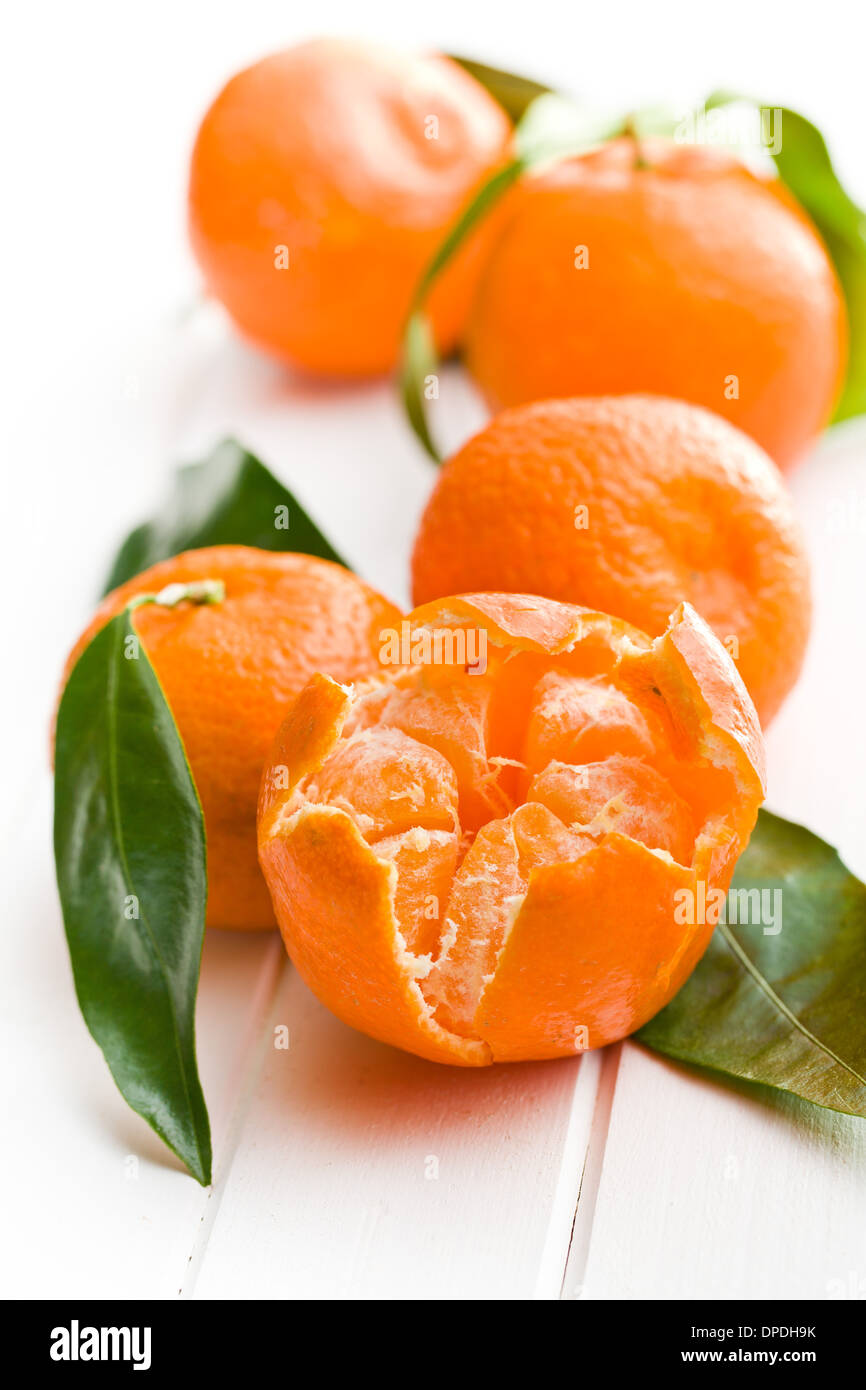 fresh mandarin with green leaves on white wooden background - Stock Image