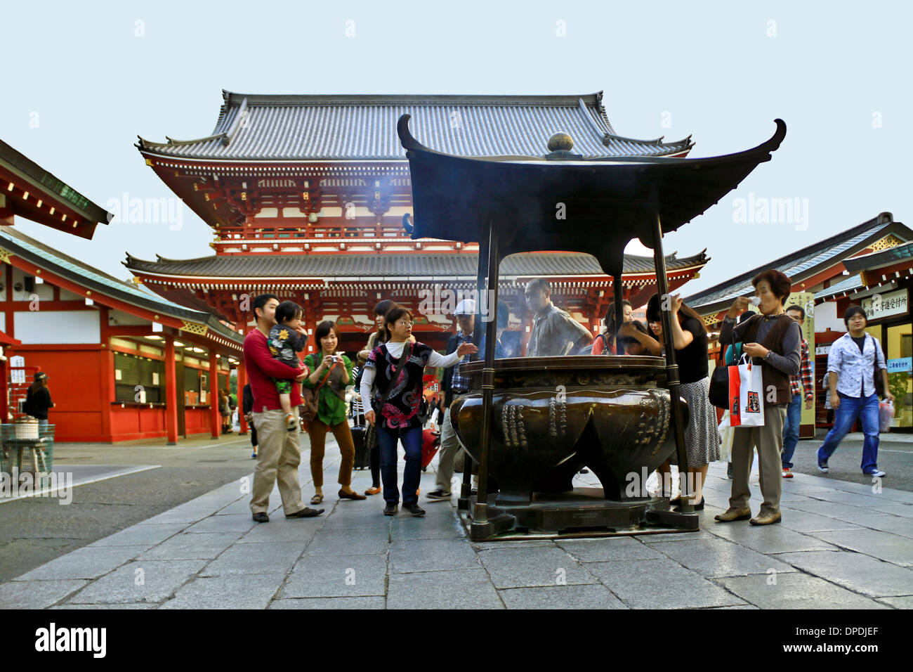 Huge censer surrounded by people, who waft incense fumes to stay healthy, at Senso-ji Temple, Asakusa, Tokyo, Japan. - Stock Image