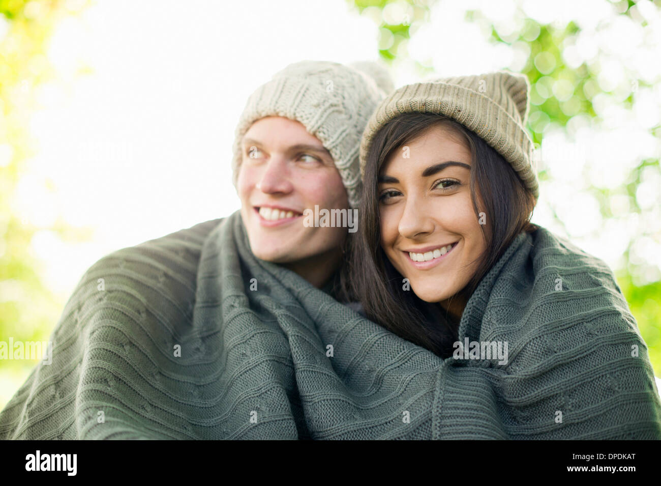 Young couple wearing knit hats wrapped in blanket - Stock Image