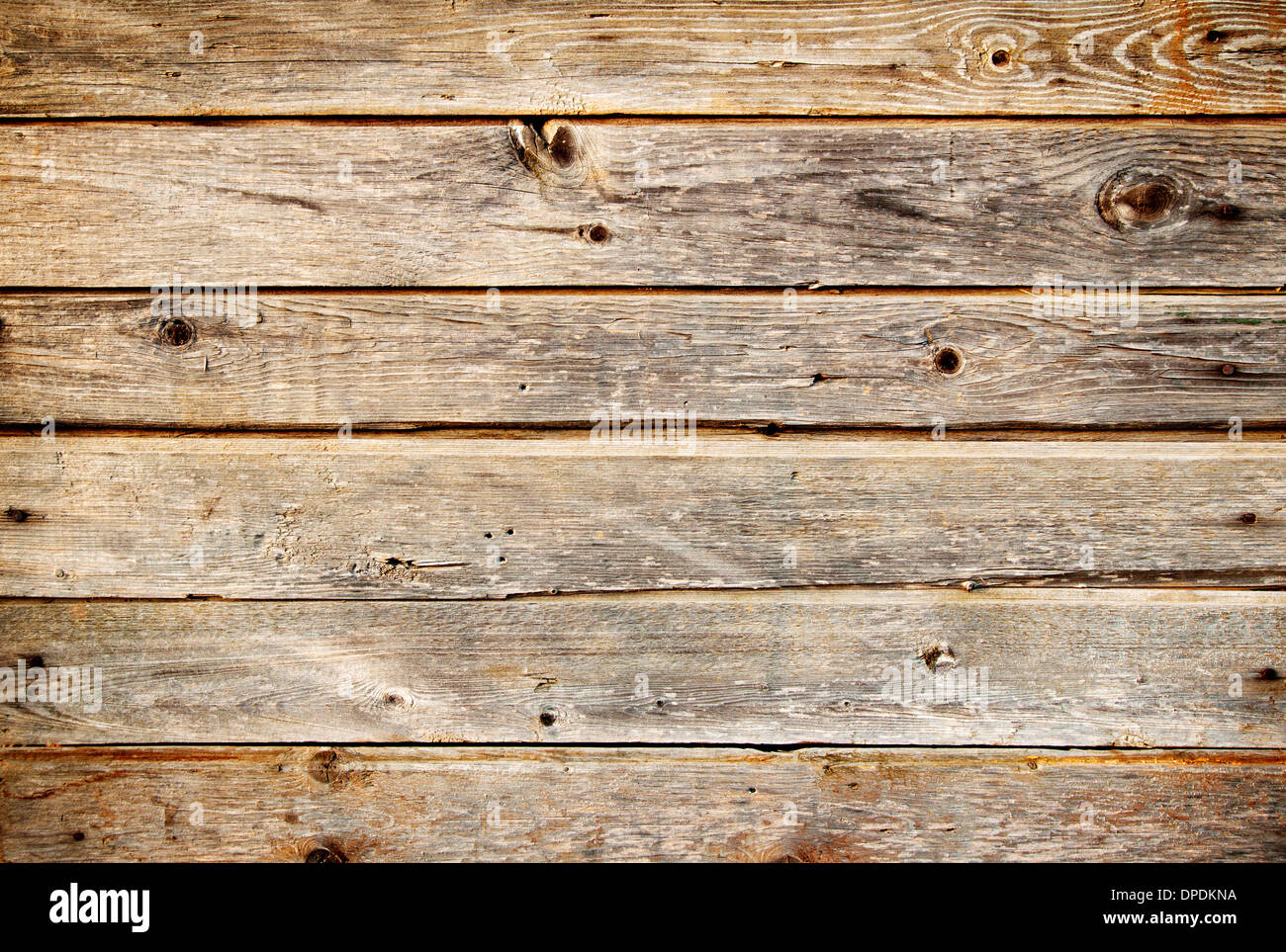 Background of coarse dark planks with knots - Stock Image