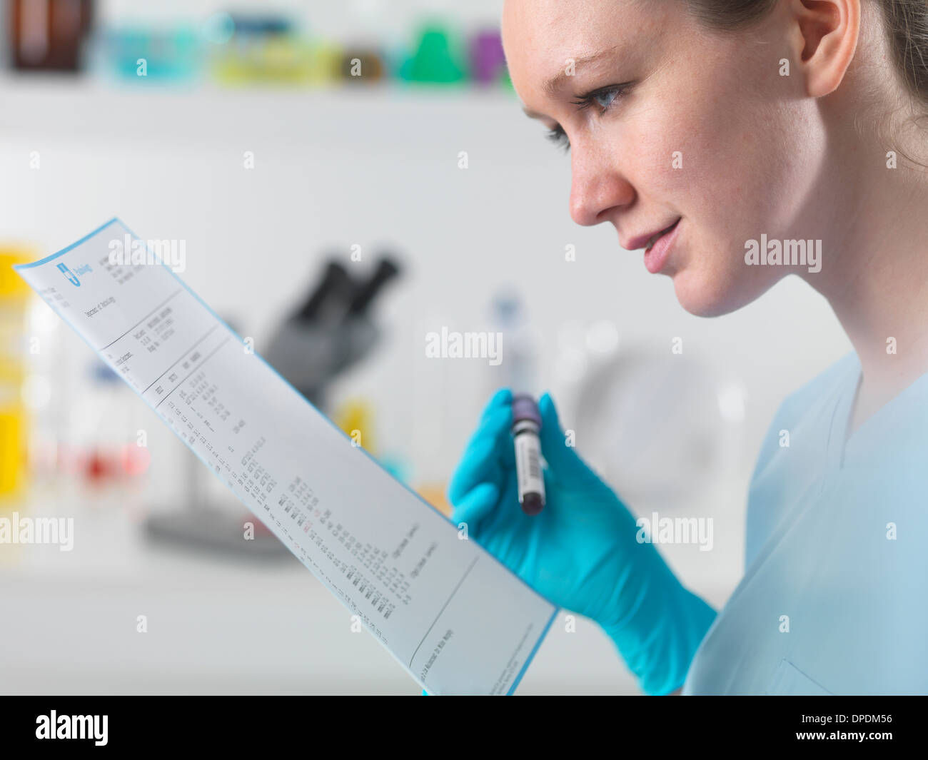 Technician holding blood sample in clinical laboratory with test results - Stock Image
