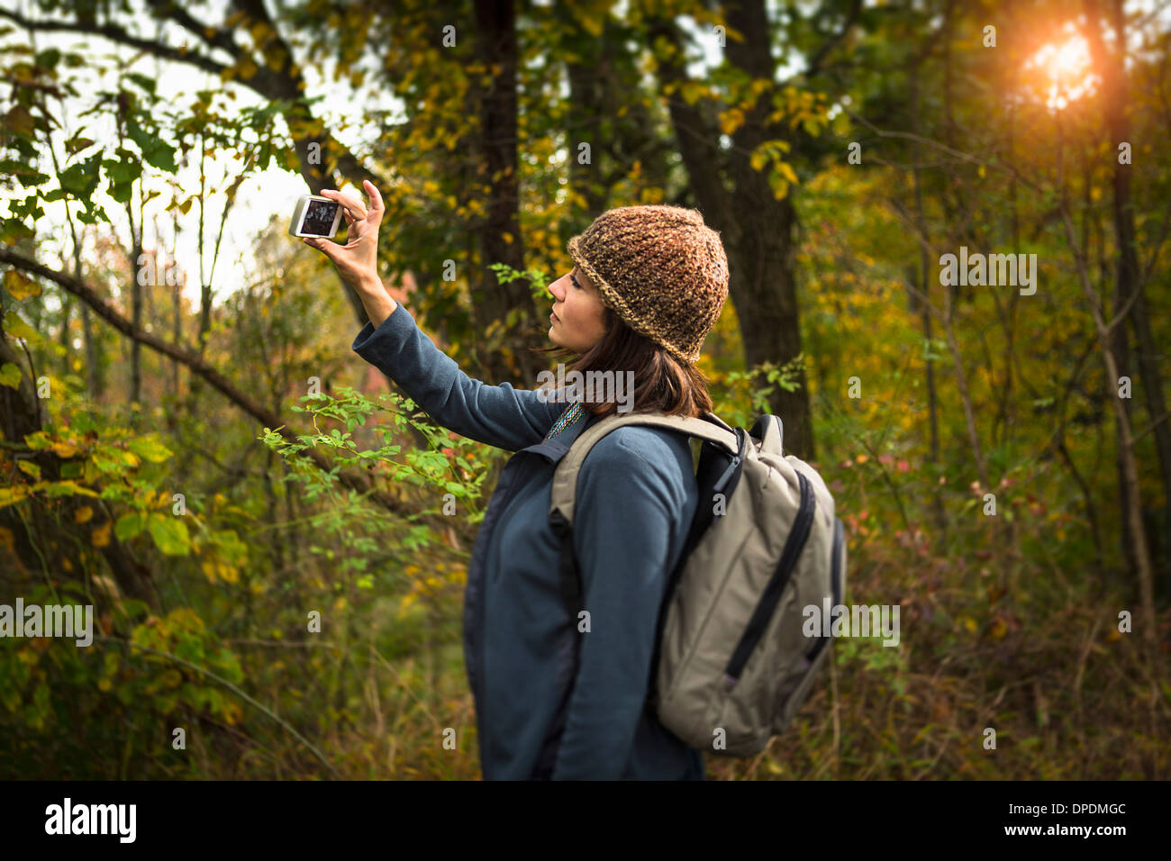 Mature woman taking photograph in forest using smartphone - Stock Image