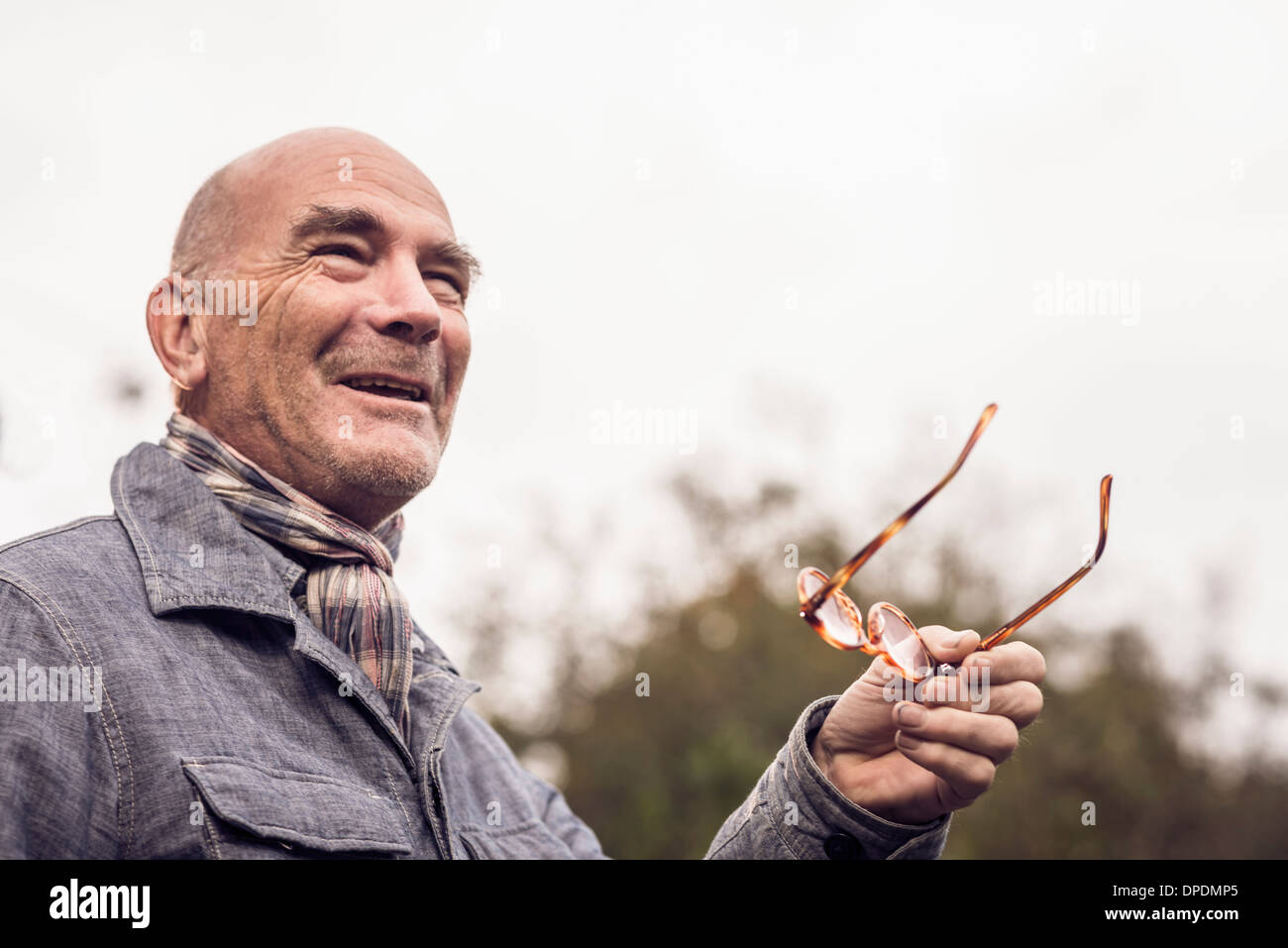 Senior man gesturing with spectacles - Stock Image