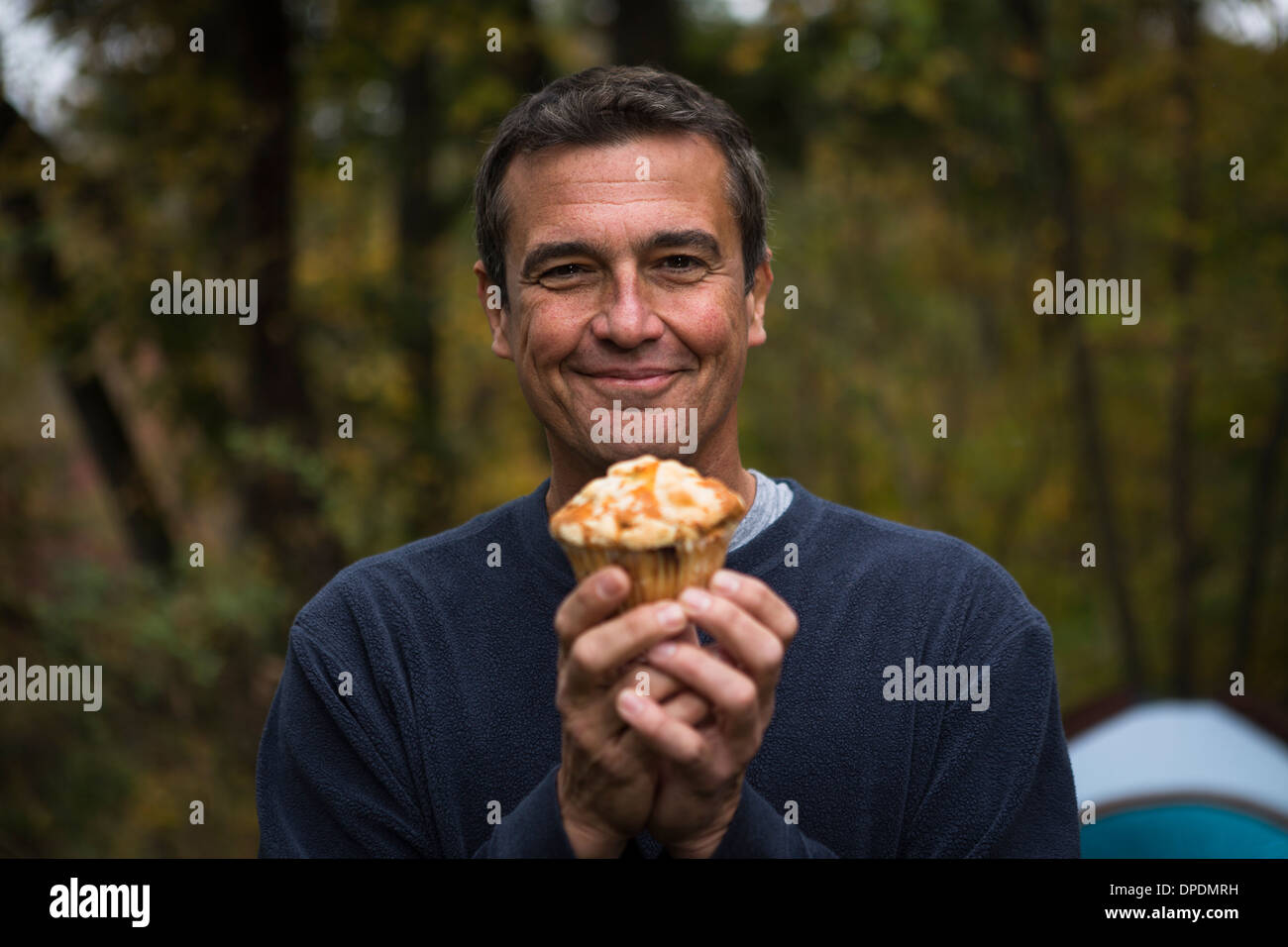 Mature man in forest holding cupcake - Stock Image