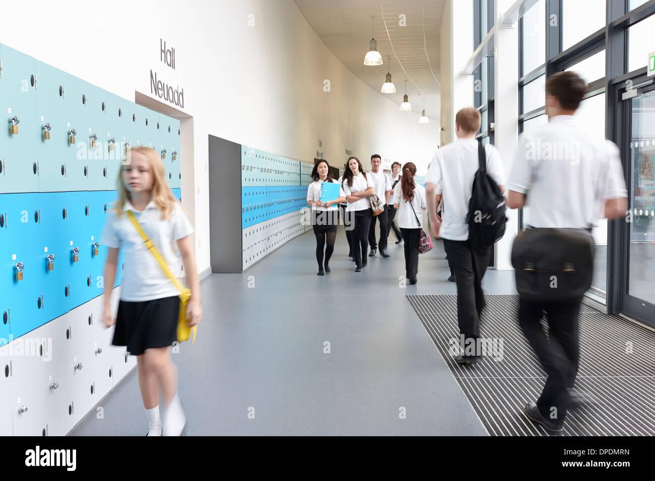 Unhappy schoolgirl walking in school corridor - Stock Image
