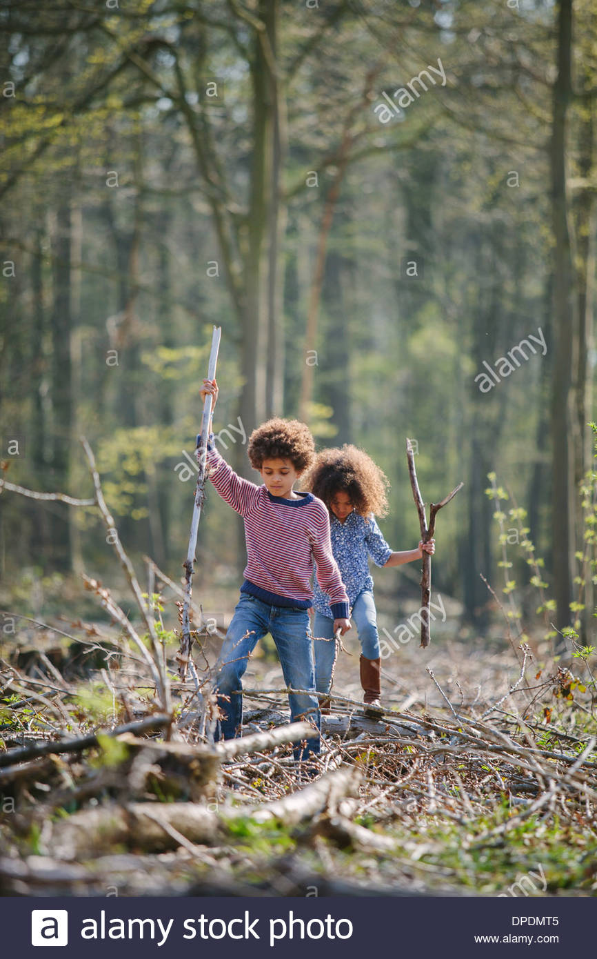 Brother and sister exploring together in woods - Stock Image